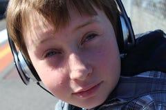 Pojke som lyssnar till musik Fotografering för Bildbyråer
