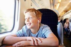 Pojke som lyssnar till musik på drevresa royaltyfri bild