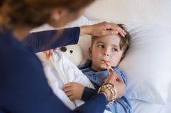 Pojke som mäter feber fotografering för bildbyråer