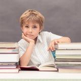 Pojke som mycket lutar hans huvud på en hand på en tabell av tjocka böcker fotografering för bildbyråer