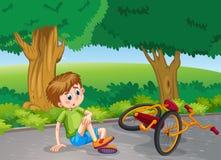 Pojke som ner faller från cykeln i parkera Arkivbilder