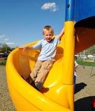 Pojke som ner glider en glidbana på parkera Royaltyfria Bilder