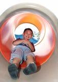 Pojke som ner glider på en cylindrisk glidbana Arkivbild
