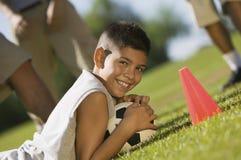 Pojke (13-15) som ner ligger på hållande fotbollboll för gräs. Arkivfoto