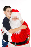 Pojke som omfamnar Santa Claus arkivbild