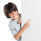 Pojke som pekar på det tomma plakatet Arkivbild