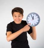 Pojke som pekar på klockan Arkivfoton