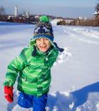 Pojke som plaing i snön Arkivfoto