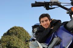 Pojke som poserar med hans motorcykel arkivbild