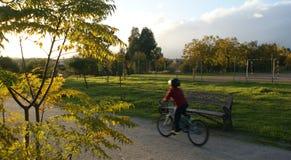 Pojke som rider en cykel på en parkeraväg Arkivbild