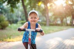 Pojke som rider en sparkcykel som ser kameran som ler, panelljus Royaltyfria Bilder