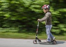 Pojke som rider hans sparkcykel Royaltyfri Foto