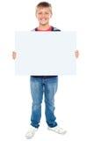 Pojke som rymmer blank whiteboard Arkivfoto
