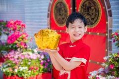 Pojke som rymmer den guld- pengarbanken Arkivbilder