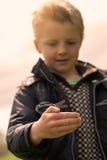 Pojke som rymmer den lilla sländan Royaltyfria Bilder