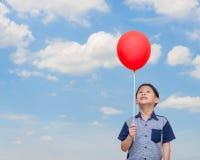 Pojke som rymmer den röda ballongen Royaltyfria Bilder
