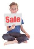 Pojke som rymmer den vita sidan med försäljningsord royaltyfria foton