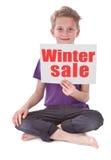 Pojke som rymmer den vita sidan med vinterförsäljningsord fotografering för bildbyråer