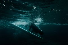Pojke som rymmer en dyk för bränningbräde under vågen royaltyfri foto