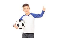 Pojke som rymmer en fotboll och ger upp en tumme Fotografering för Bildbyråer