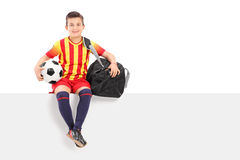 Pojke som rymmer en fotboll och sitter på panel Arkivbild