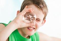 Pojke som rymmer en mång- fasetterad kristall mot öga Royaltyfria Foton