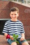 Pojke som rymmer en ros och le Begreppet av förälskelse Royaltyfria Bilder