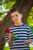 Pojke som rymmer en ros och le Begreppet av förälskelse Royaltyfri Foto
