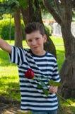 Pojke som rymmer en ros och le Begreppet av förälskelse Royaltyfria Foton
