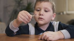 Pojke som rymmer en säkerhetsmatch och blåser in i flamman långsam rörelse stock video