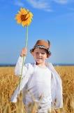 Pojke som rymmer en solros i mitt av ett fält Fotografering för Bildbyråer
