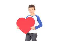 Pojke som rymmer en stor röd hjärta Arkivfoto