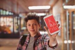 Pojke som rymmer en telefon med skolasymboler på skärmen Royaltyfri Fotografi