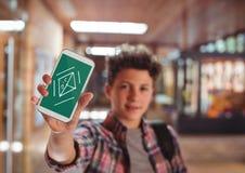 Pojke som rymmer en telefon med skolasymboler på skärmen Fotografering för Bildbyråer