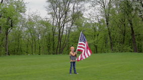 Pojke som rymmer ett baner av USA stock video