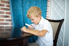 Pojke som rymmer ett förstoringsglas royaltyfri foto