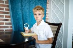 Pojke som rymmer ett förstoringsglas royaltyfri bild