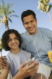 Pojke (13-15) som rymmer fadern för spelare för bärbar musik som lyssnar med hörlurar och innehavexponeringsglas av ståenden för f Royaltyfria Bilder