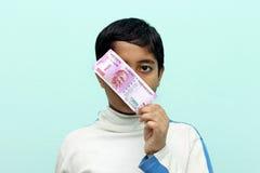 Pojke som rymmer 2000 nya indiska pengar för rupie i hans hand Royaltyfri Fotografi