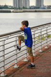 Pojke som ser över räcket arkivbild
