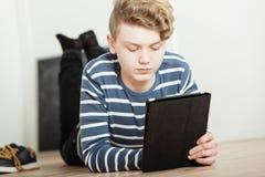 Pojke som ser datorminnestavlan Fotografering för Bildbyråer