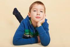 Pojke som ser in i kameran och tänka. Arkivbild