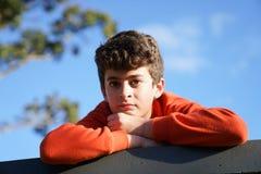 Pojke som ser, medan framåt vila överst av väggen Arkivfoto
