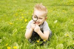 Pojke som ser till och med ett förstoringsglas och ett leende Arkivfoton
