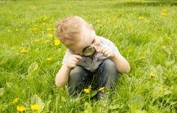Pojke som ser till och med ett förstoringsglas på gräset Arkivbilder