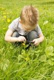 Pojke som ser till och med ett förstoringsglas på gräset Royaltyfri Foto
