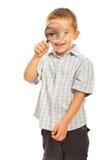 Pojke som ser till och med förstoringsapparat Fotografering för Bildbyråer