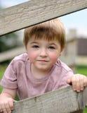 Pojke som ser till och med staketmellanrum. Arkivfoto