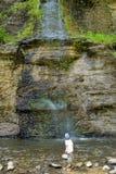 Pojke som ser upp på klippor som sipprar vattenfallet fotografering för bildbyråer