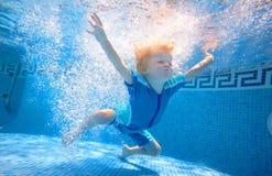 pojke som simmar undervattens- barn Arkivbilder